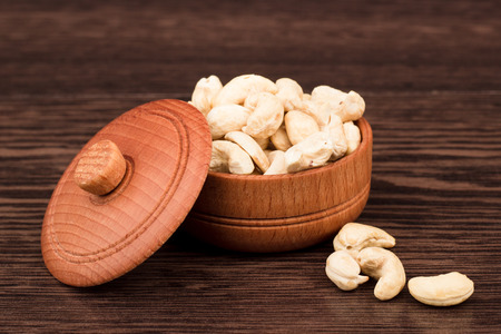 39018596 - nuts in a wooden bowl on a wooden background. healthy eating